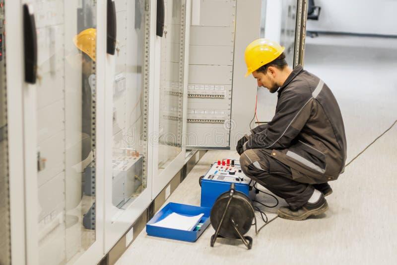 L'ingegnere di manutenzione ispeziona il sistema con i equipmen stabiliti della prova del relè fotografie stock