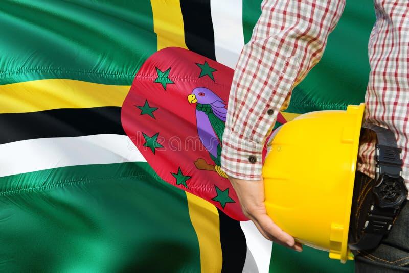 L'ingegnere domenicano sta tenendo il casco di sicurezza giallo con l'ondeggiamento del fondo della bandiera della Dominica Conce fotografia stock