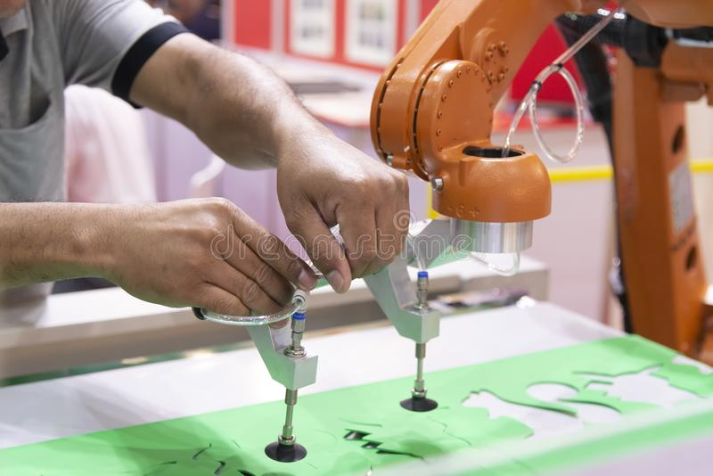 L'ingegnere ha installato il braccio del robot nella fabbrica d'imballaggio immagine stock libera da diritti