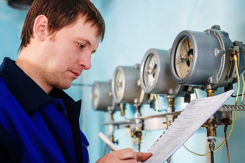 L'ingegnere, lavoratore registra le letture dei sensori e dei manometri Controllo del rifornimento idrico e del sistema di riscal immagini stock libere da diritti