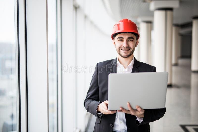 L'ingegnere maschio bello sta utilizzando un taccuino per lavoro immagine stock
