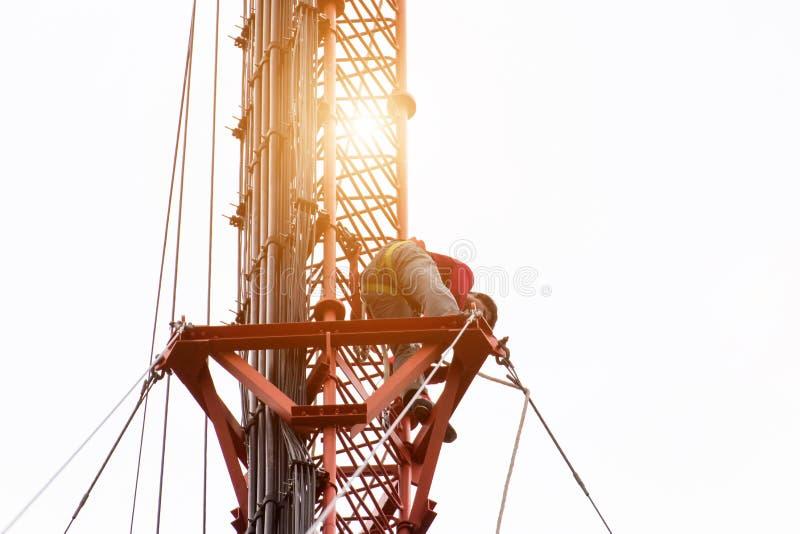 L'ingegnere o il tecnico che lavora all'alta torre, lavoro di rischio di alto lavoro, la gente sta lavorando con l'attrezzatura d fotografia stock