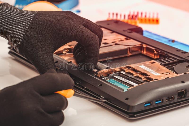 L'ingegnere smantella i dettagli di un computer portatile rotto per la riparazione immagine stock libera da diritti