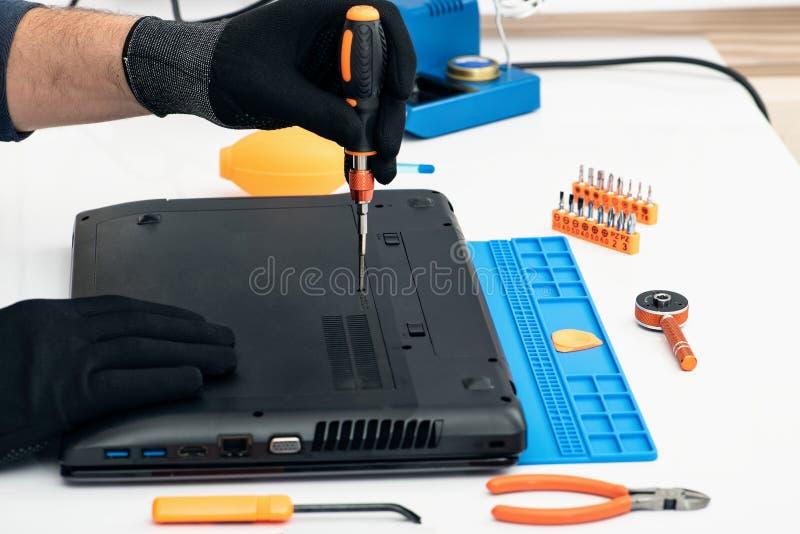 L'ingegnere smantella i dettagli di un computer portatile rotto per la riparazione fotografia stock