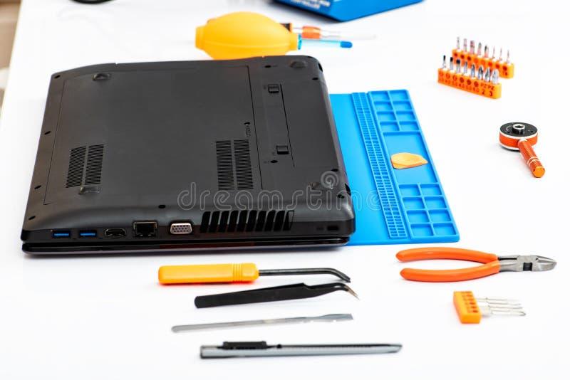 L'ingegnere smantella i dettagli di un computer portatile rotto per la riparazione immagini stock libere da diritti