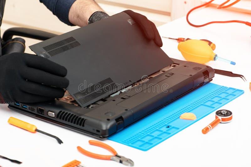 L'ingegnere smantella i dettagli di un computer portatile rotto per la riparazione immagini stock