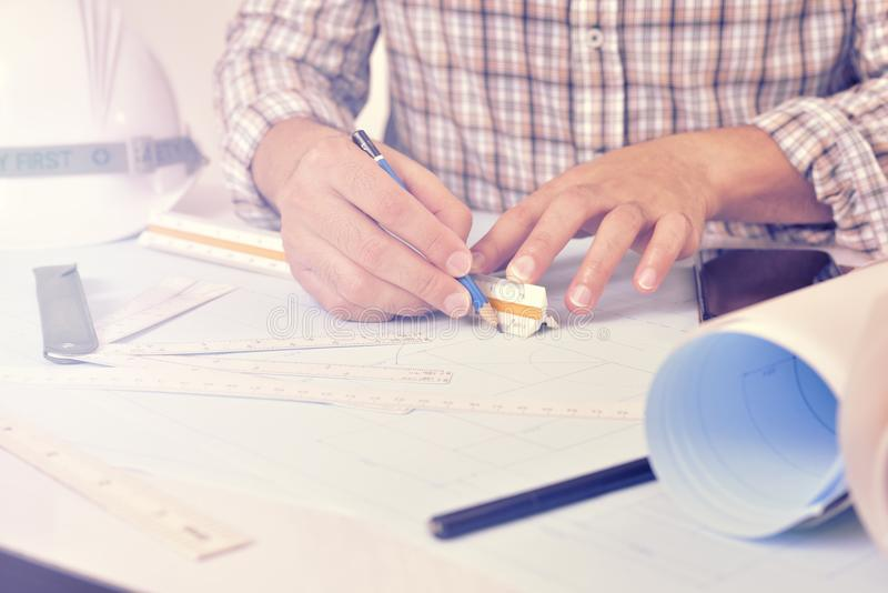 L'ingegnere sta lavorando allo scrittorio con il piano del disegno immagine stock