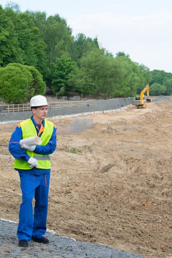 L'ingegnere tiene in sua mano un modello per la costruzione di nuovo edificio fotografia stock libera da diritti