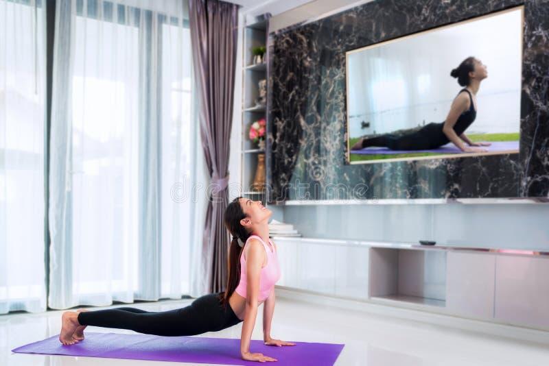 L'inizio asiatico di signora ad yoga di formazione vicino segue la vettura in televisione fotografie stock libere da diritti