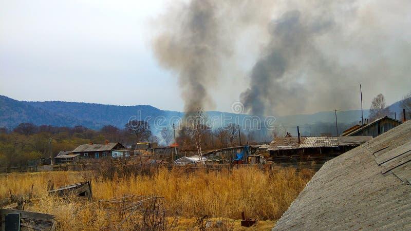 L'inizio di grande fuoco nella sera nel villaggio fotografia stock