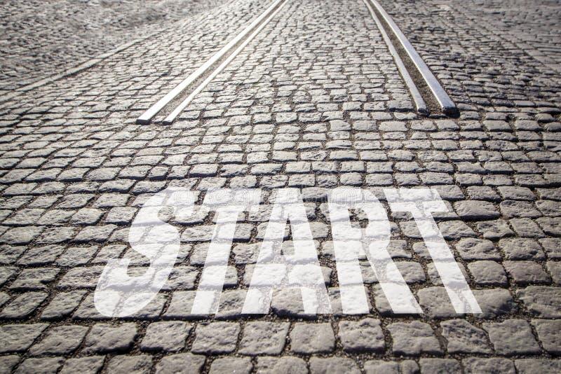 L'INIZIO di parola è scritto sulla strada pavimentata cobbled con le rotaie - l'inizio della strada, nuova vita fotografia stock libera da diritti