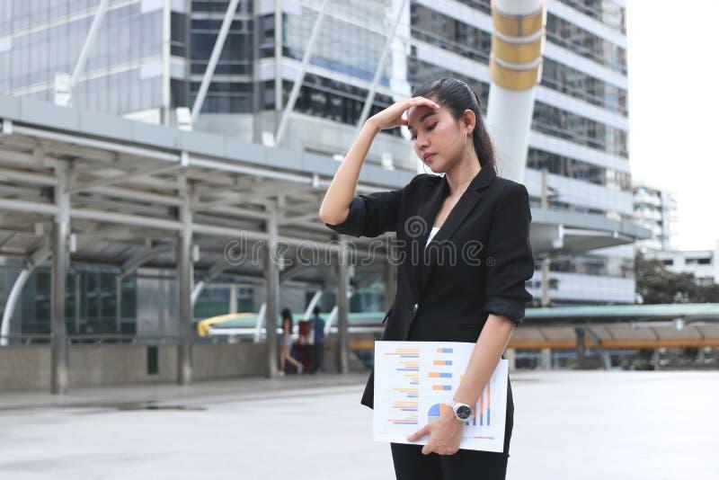 L'inquiétude a soumis à une contrainte la jeune femme asiatique d'affaires dans la dépression dehors image libre de droits