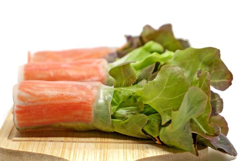 L'insalata arriva a fiumi la tagliatella con la carota e gli ortaggi freschi sul piatto di legno e sul fondo bianco fotografie stock