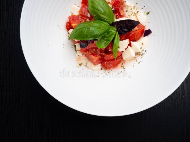 L'insalata caprese deliziosa con i pomodori ed il formaggio maturi della mozzarella con basilico fresco va Alimento italiano fotografia stock