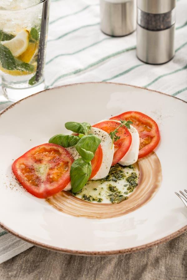 L'insalata caprese deliziosa con i pomodori ed il formaggio maturi della mozzarella con le foglie fresche del basilico è servito  immagine stock libera da diritti