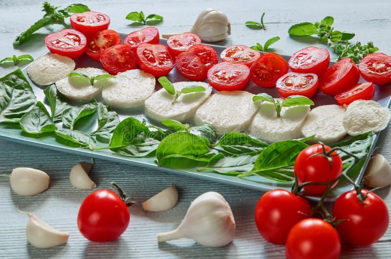 L'insalata caprese sana con il formaggio affettato della mozzarella, pomodori ciliegia, basilico fresco va, aglio Alimento italia immagini stock libere da diritti