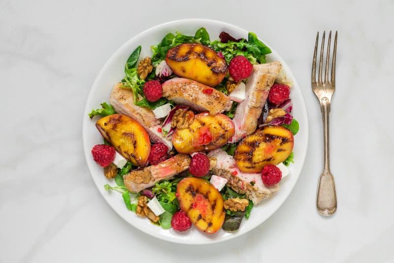 L'insalata della vitamina con il pollo arrostito e pesca, il feta, i lamponi, le noci ed il lampone sauce in un piatto fotografia stock libera da diritti