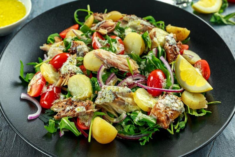 L'insalata dello sgombro affumicato con la patata novella bollita calda, pomodori ciliegia, ha tagliato la cipolla rossa e Ruccol immagine stock