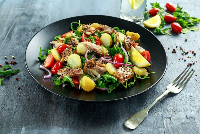L'insalata dello sgombro affumicato con la patata novella bollita calda, pomodori ciliegia, ha tagliato la cipolla rossa e Ruccol immagini stock