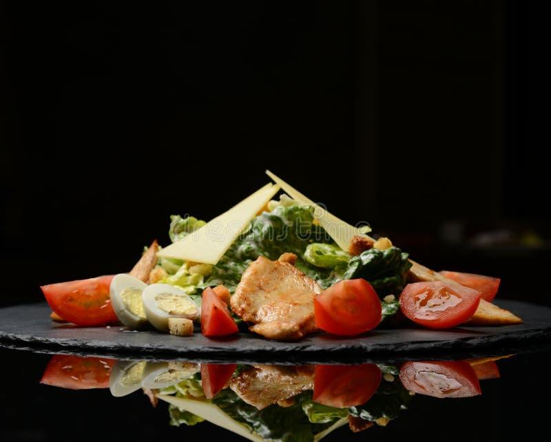 L'insalata di Caesar con il petto di pollo grigliato crostini ha grattato il parmigiano e la lattuga romana con salsa sul piatto  immagine stock