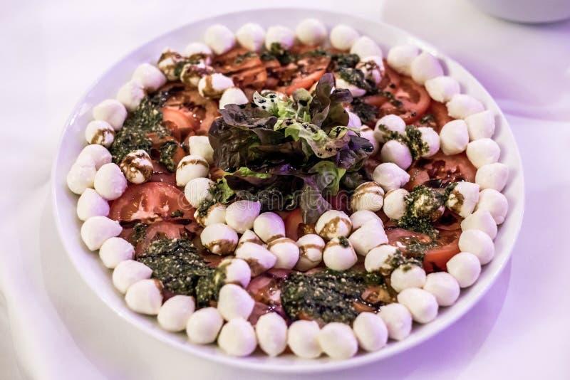 L'insalata di Caprese con il pomodoro della mozzarella, il basilico e l'aceto balsamico ha sistemato sul piatto bianco immagini stock