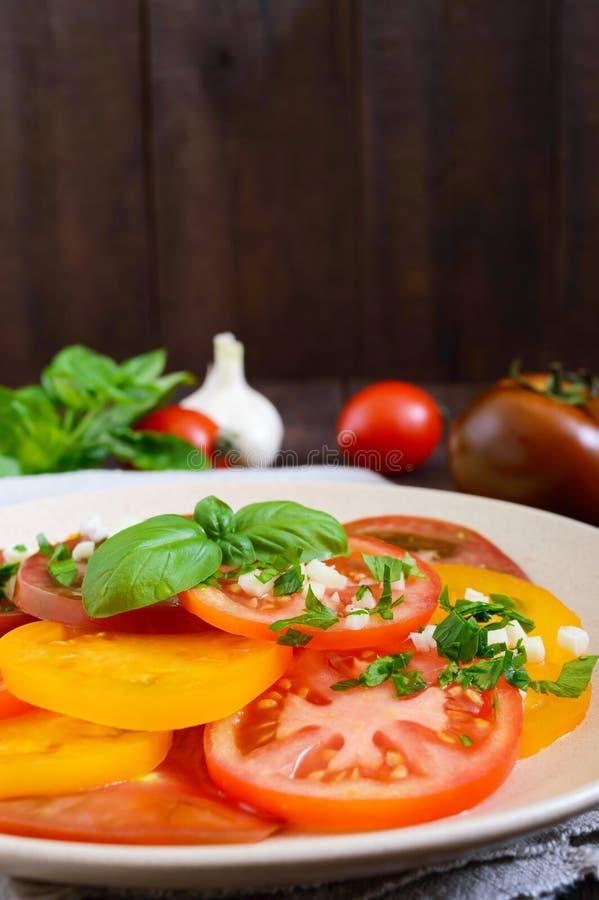 L'insalata piccante dei pomodori gialli, rossi, neri, incide i cerchi con aglio ed i verdi su un piatto fotografia stock