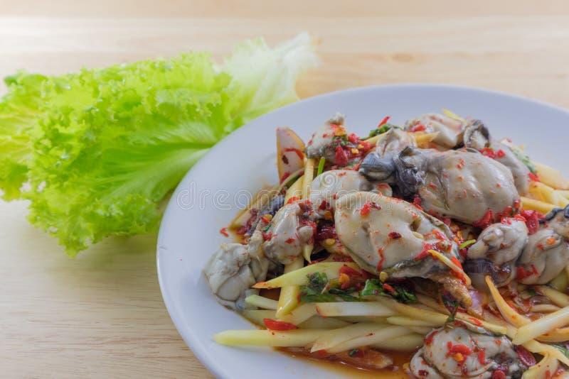 L'insalata piccante dell'ostrica in piatto ha messo sopra il piatto di legno immagine stock libera da diritti