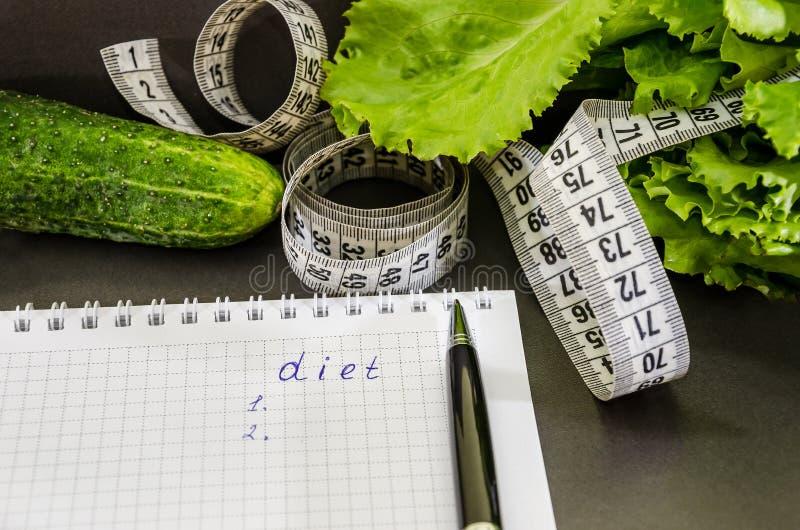 """L'inscription """"régime """"sur un carnet, des dollars, des pièces de monnaie et des légumes sur la table photos libres de droits"""