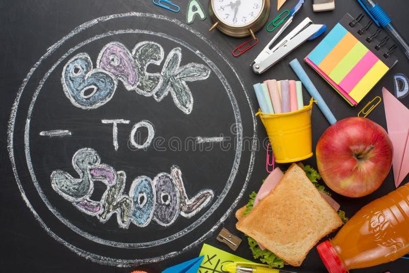 L'inscription de nouveau à l'école, sur un conseil pédagogique avec les poignées, la craie, un réveil, et le petit déjeuner d'éco photos stock