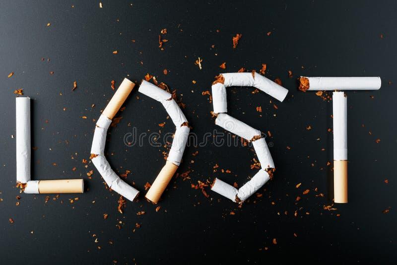 L'inscription A PERDU des cigarettes sur un fond noir Cessez le fumage Le concept des mises ? mort de tabagisme Inscription de mo image libre de droits