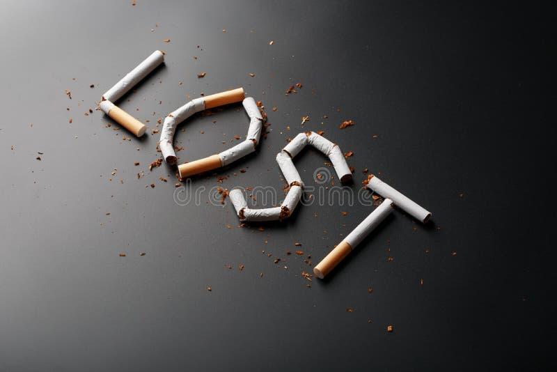 L'inscription A PERDU des cigarettes sur un fond noir Cessez le fumage Le concept des mises ? mort de tabagisme Inscription de mo photos stock