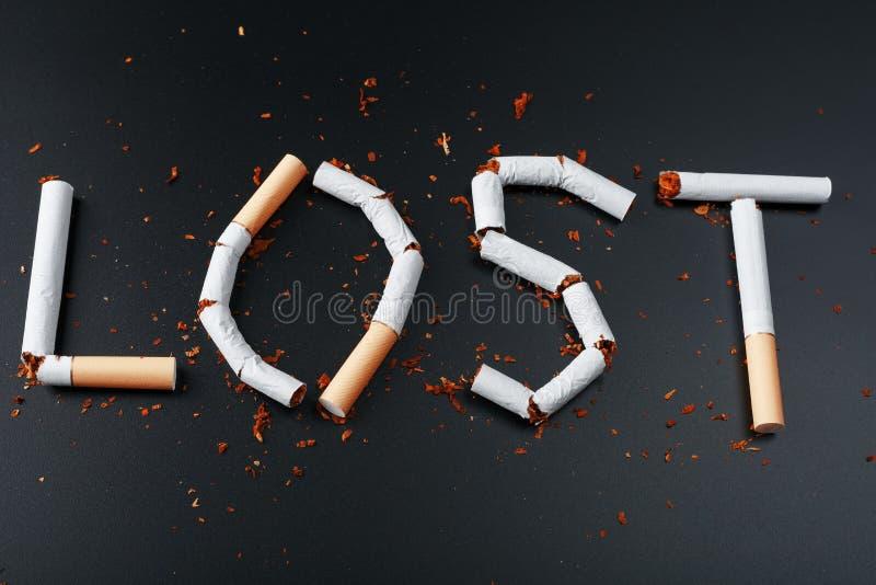 L'inscription A PERDU des cigarettes sur un fond noir Cessez le fumage Le concept des mises ? mort de tabagisme Inscription de mo photo libre de droits