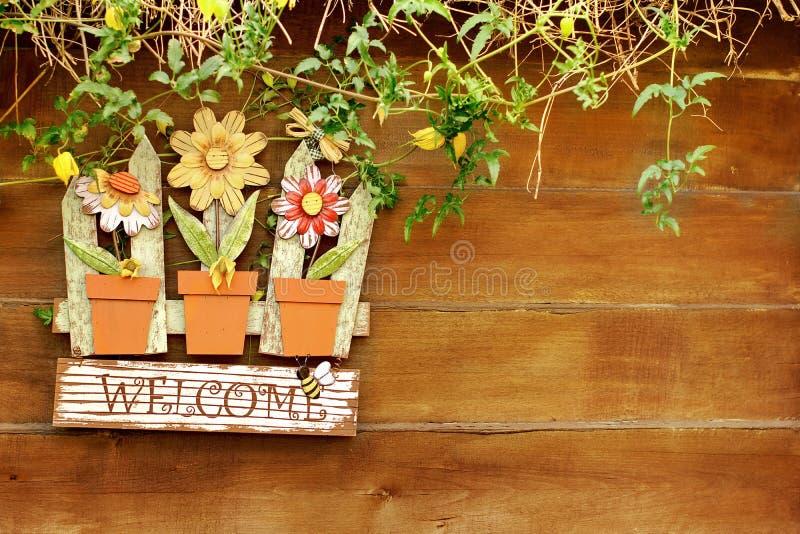 L'insegna benvenuta su di legno recinta il giardino immagine stock