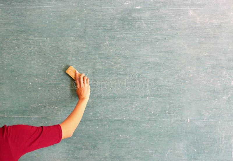L'insegnante asiatico cancella sulla lavagna con la gomma del bordo in aula, concetto di istruzione immagini stock libere da diritti