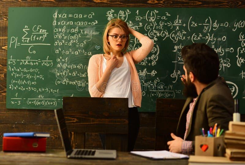 L'insegnante attento che parla con suo studente nella classe di scienza all'università, buona ricerca degli insegnanti ha impegna immagine stock libera da diritti