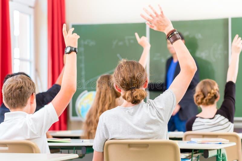L'insegnante classe A dell'insegnamento o istruisce di allievi a scuola fotografia stock