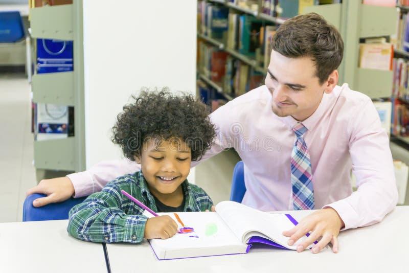 L'insegnante dell'uomo e lo studente del bambino imparano con il libro al backgro dello scaffale per libri immagine stock libera da diritti