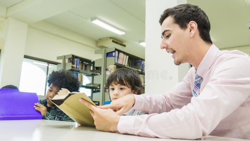 L'insegnante dell'uomo e lo studente del bambino imparano con il libro al backgro dello scaffale per libri immagine stock