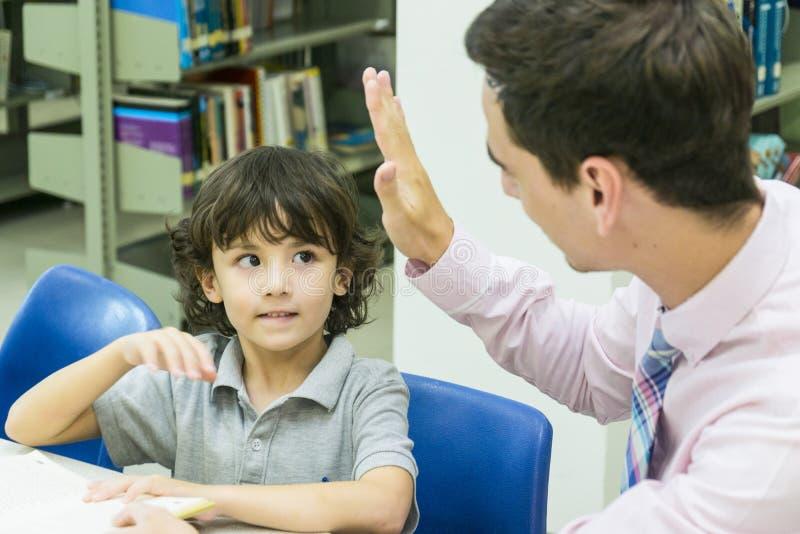 L'insegnante dell'uomo e lo studente del bambino imparano con il libro al backgro dello scaffale per libri fotografie stock libere da diritti