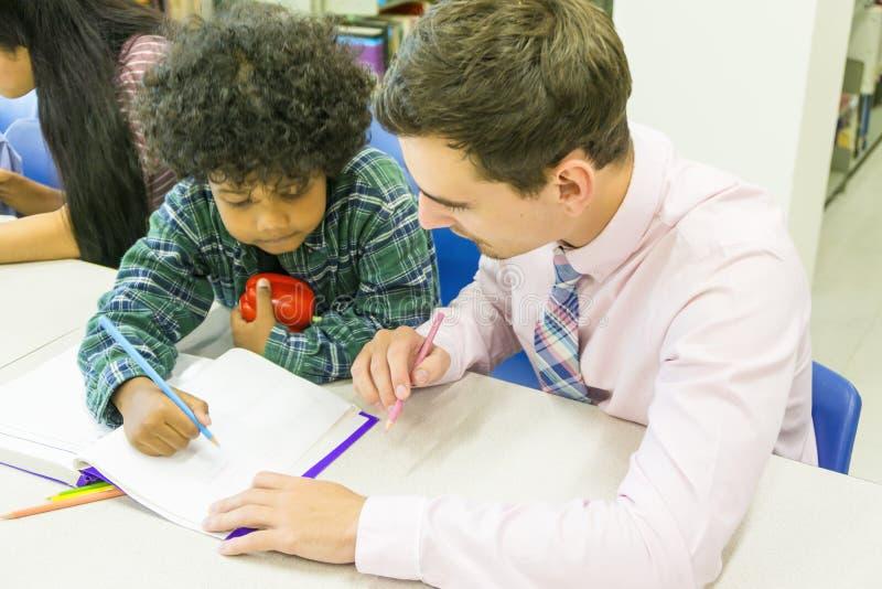 L'insegnante dell'uomo e lo studente del bambino imparano con il libro al backgro dello scaffale per libri immagini stock libere da diritti