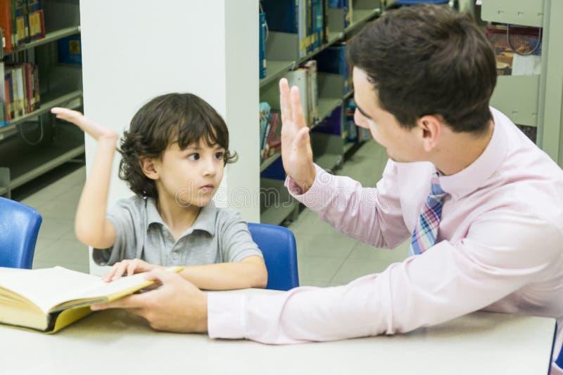 L'insegnante dell'uomo e lo studente del bambino imparano con il libro al backgro dello scaffale per libri fotografia stock libera da diritti