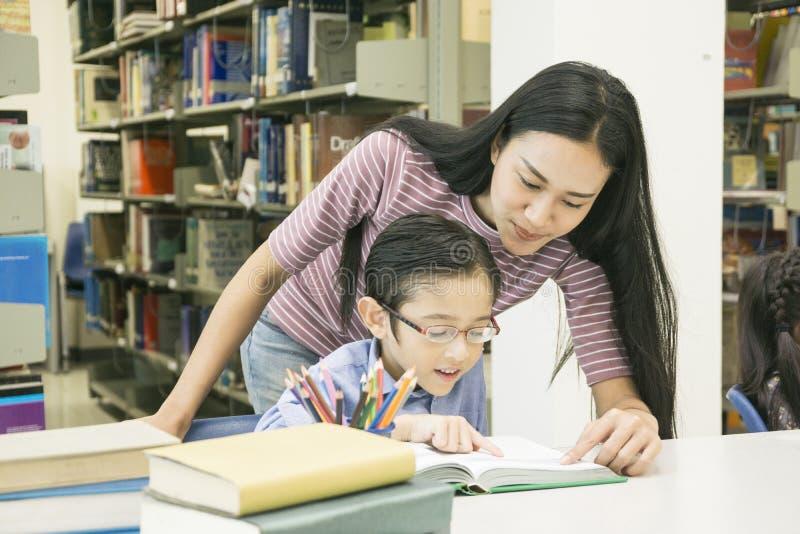 L'insegnante della donna e lo studente del bambino imparano con il libro al backg dello scaffale per libri fotografie stock