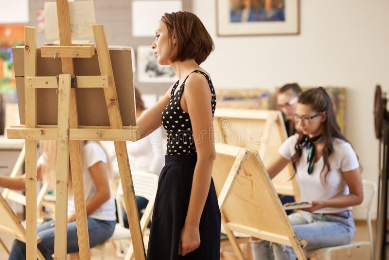 L'insegnante di disegno incantante nel bello vestito mostra la tecnica di disegno al cavalletto nello studio di arte fotografia stock