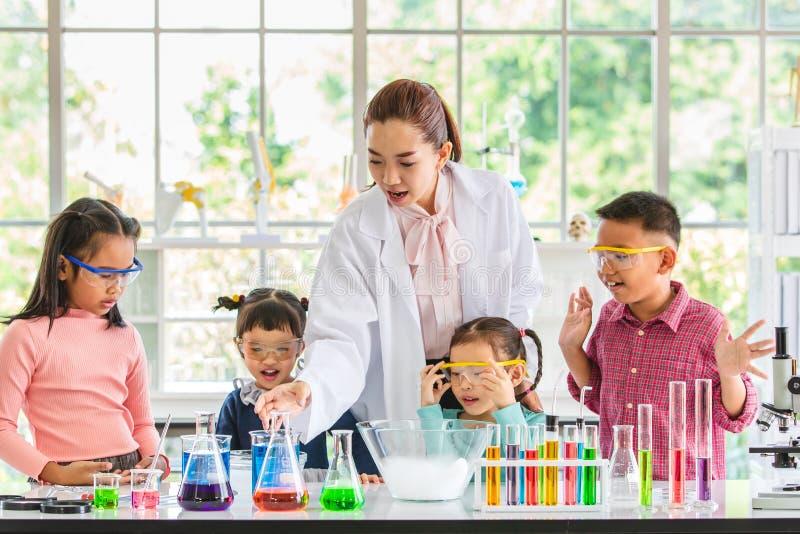 L'insegnante insegna agli studenti circa i prodotti chimici in laboratorio fotografia stock libera da diritti