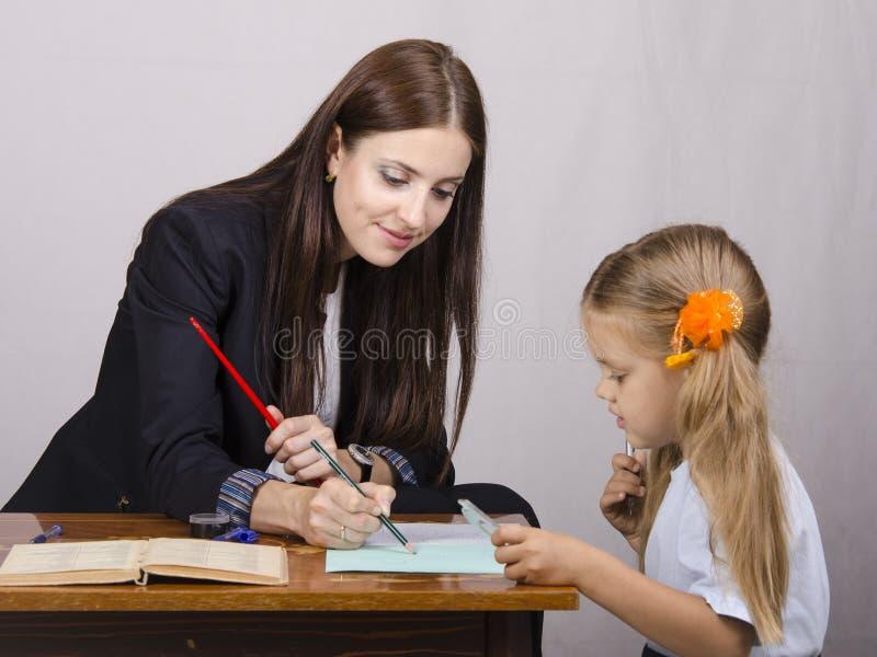 L insegnante insegna alle lezioni con uno studente che si siede alla tavola