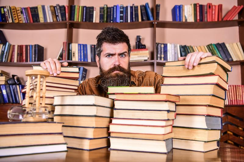 L'insegnante o lo studente con la barba si siede alla tavola con i libri, defocused Uomo sul fronte serio fra i mucchi dei libri, fotografia stock libera da diritti