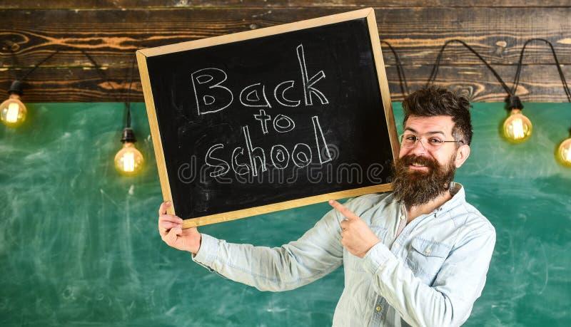 L'insegnante in occhiali tiene la lavagna con il titolo di nuovo alla scuola Concetto di noleggio degli insegnanti Uomo con la ba immagine stock libera da diritti