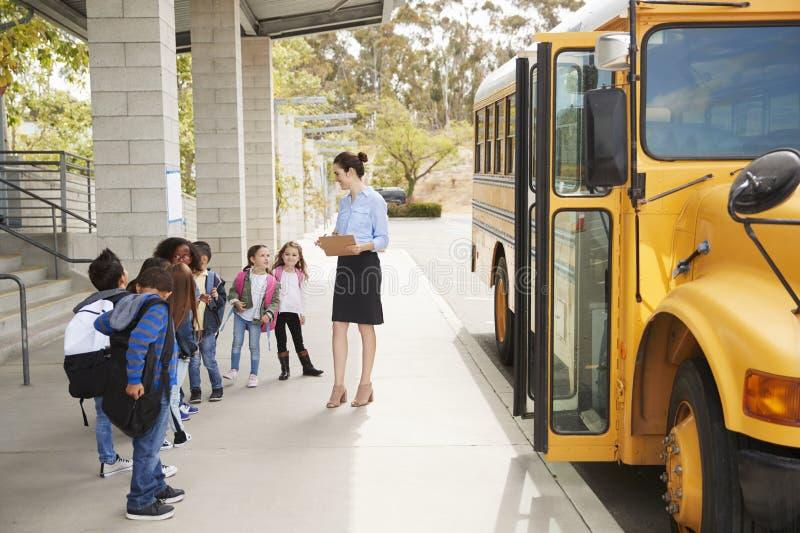 L'insegnante parla con giovani bambini della scuola in scuolabus, vista laterale fotografie stock