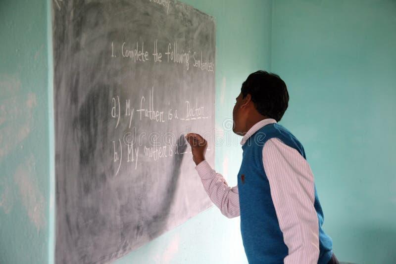 L'insegnante scrive sulla lavagna immagine stock libera da diritti