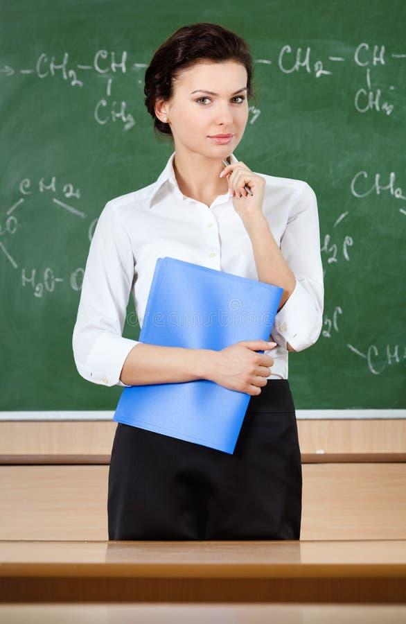 L'insegnante serio è vicino alla lavagna immagini stock